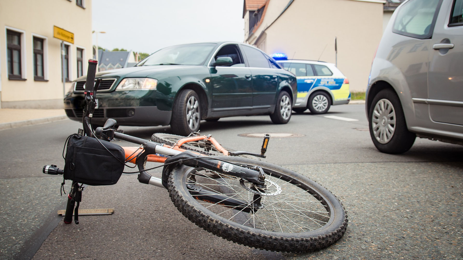 bicycle lying on road with vehicles in background