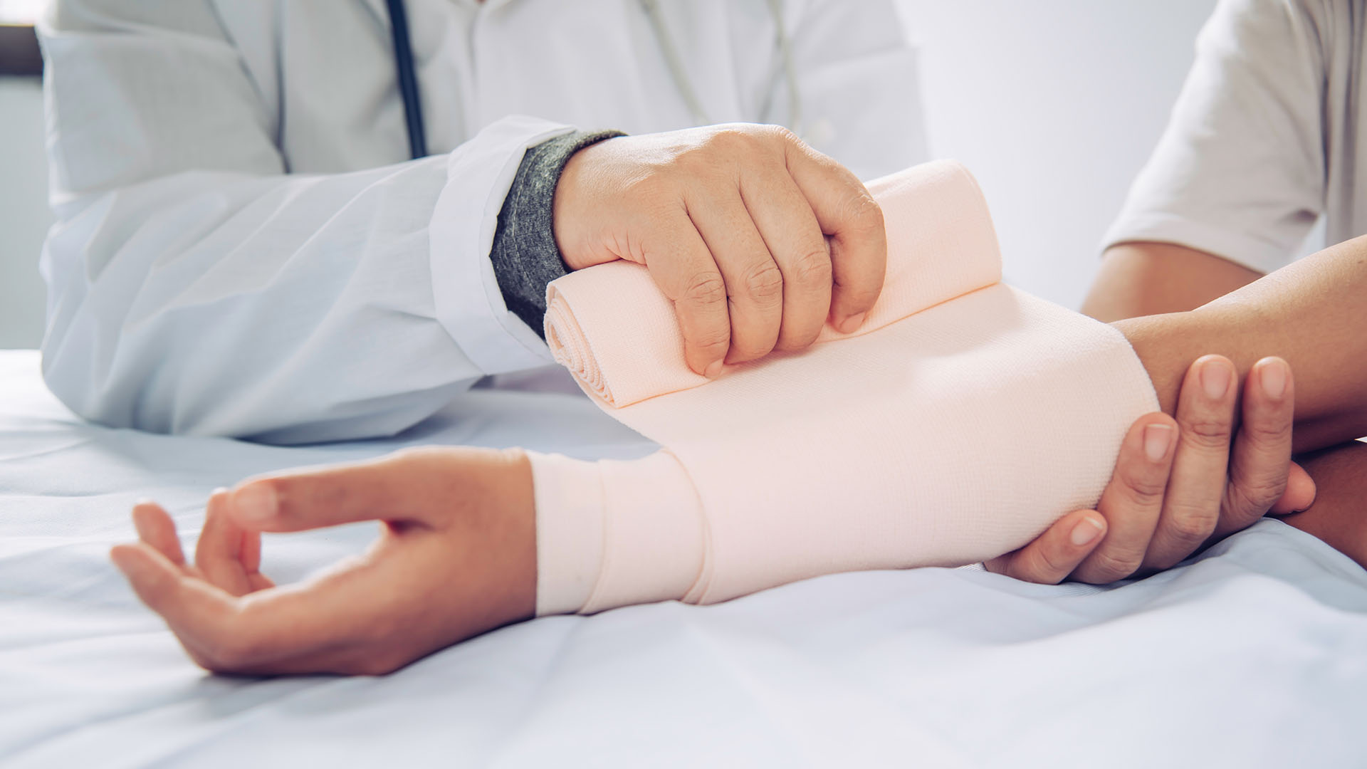 doctor wraps a burn injury on patients arm