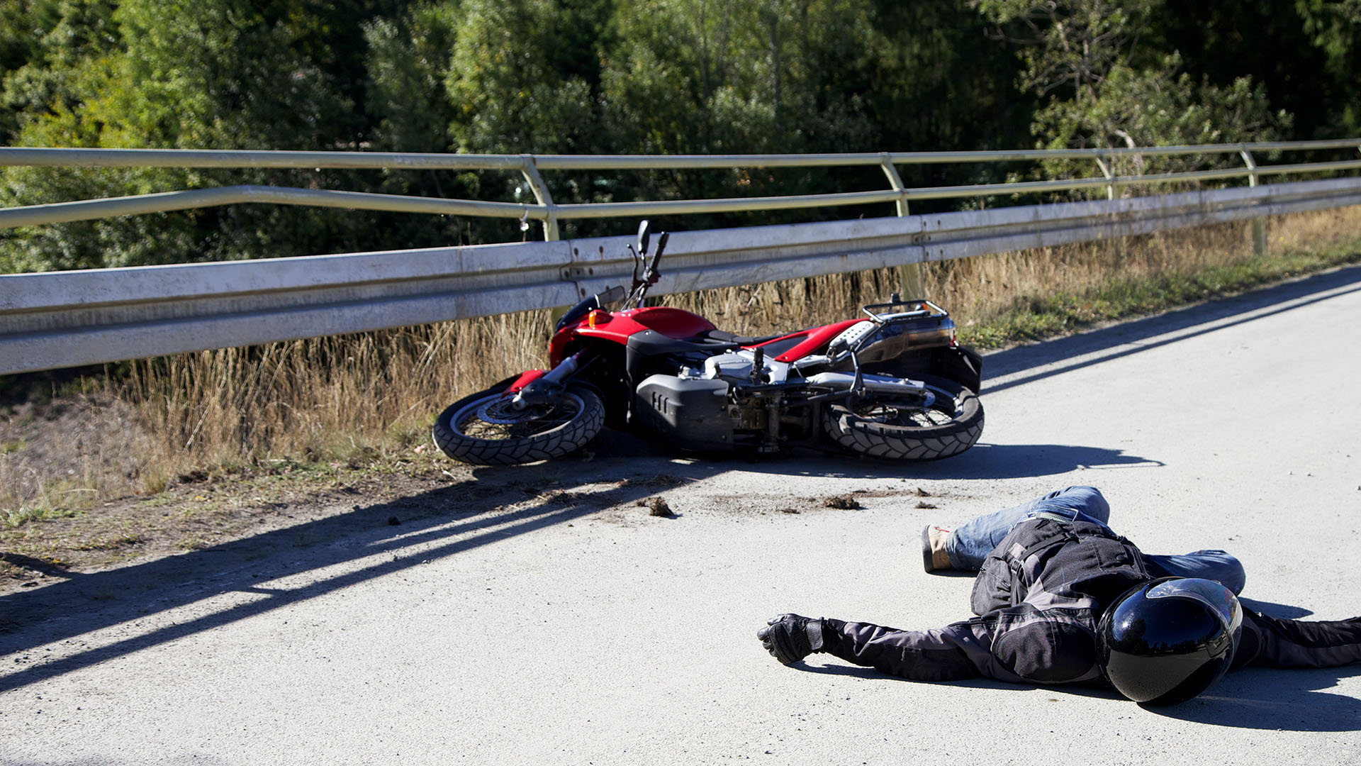 rider and motorcycle lying on the road after a crash