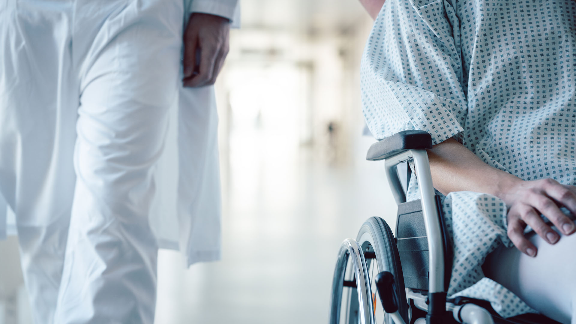 patient in wheelchair with doctor in hospital hallway