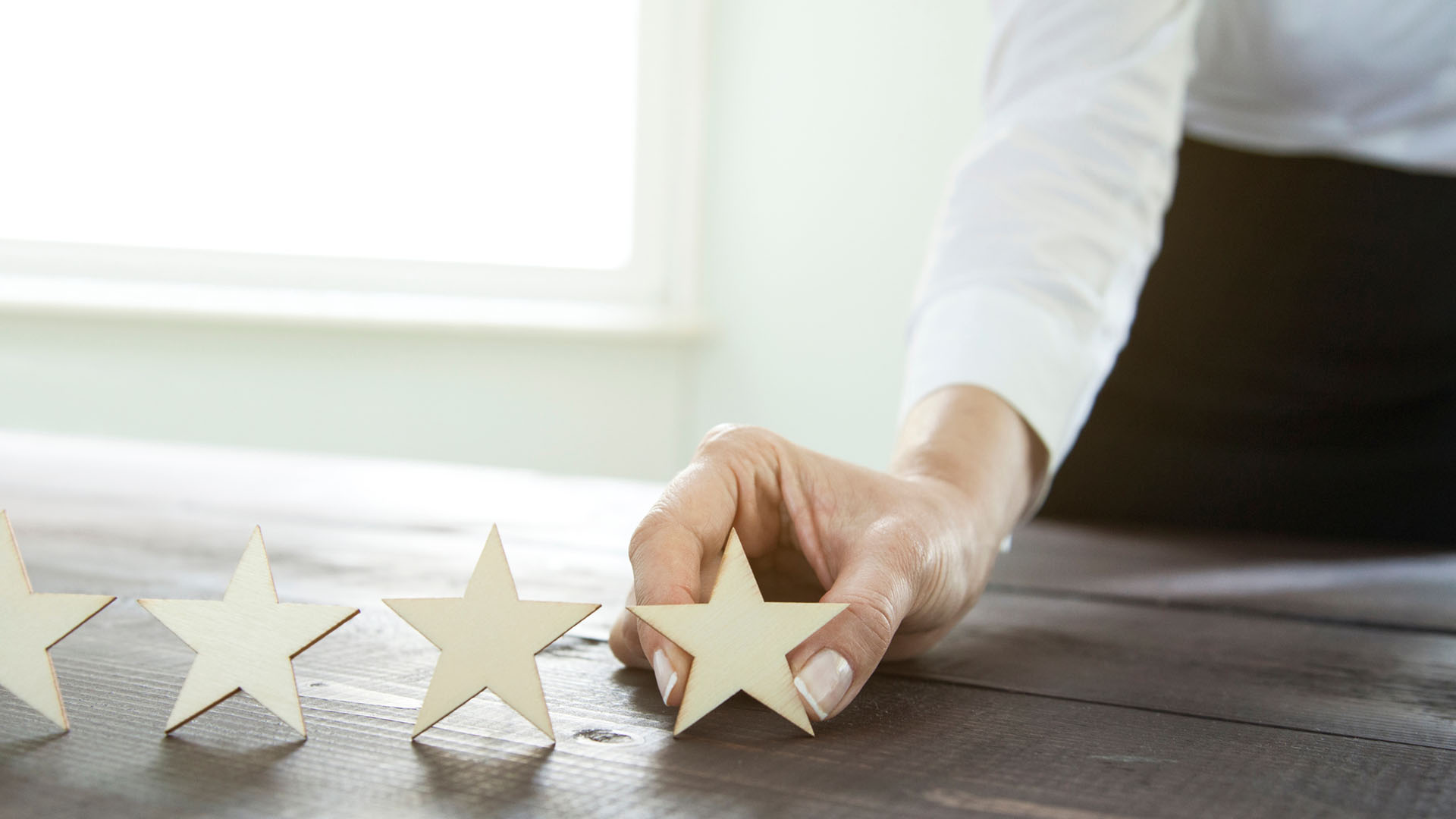 woman's hand placing wooden stars in a row