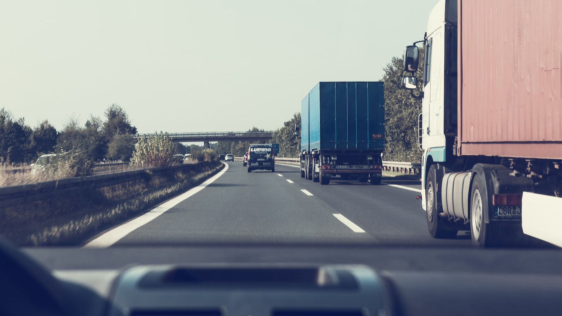 view of trucks driving on highway from inside of a vehicle