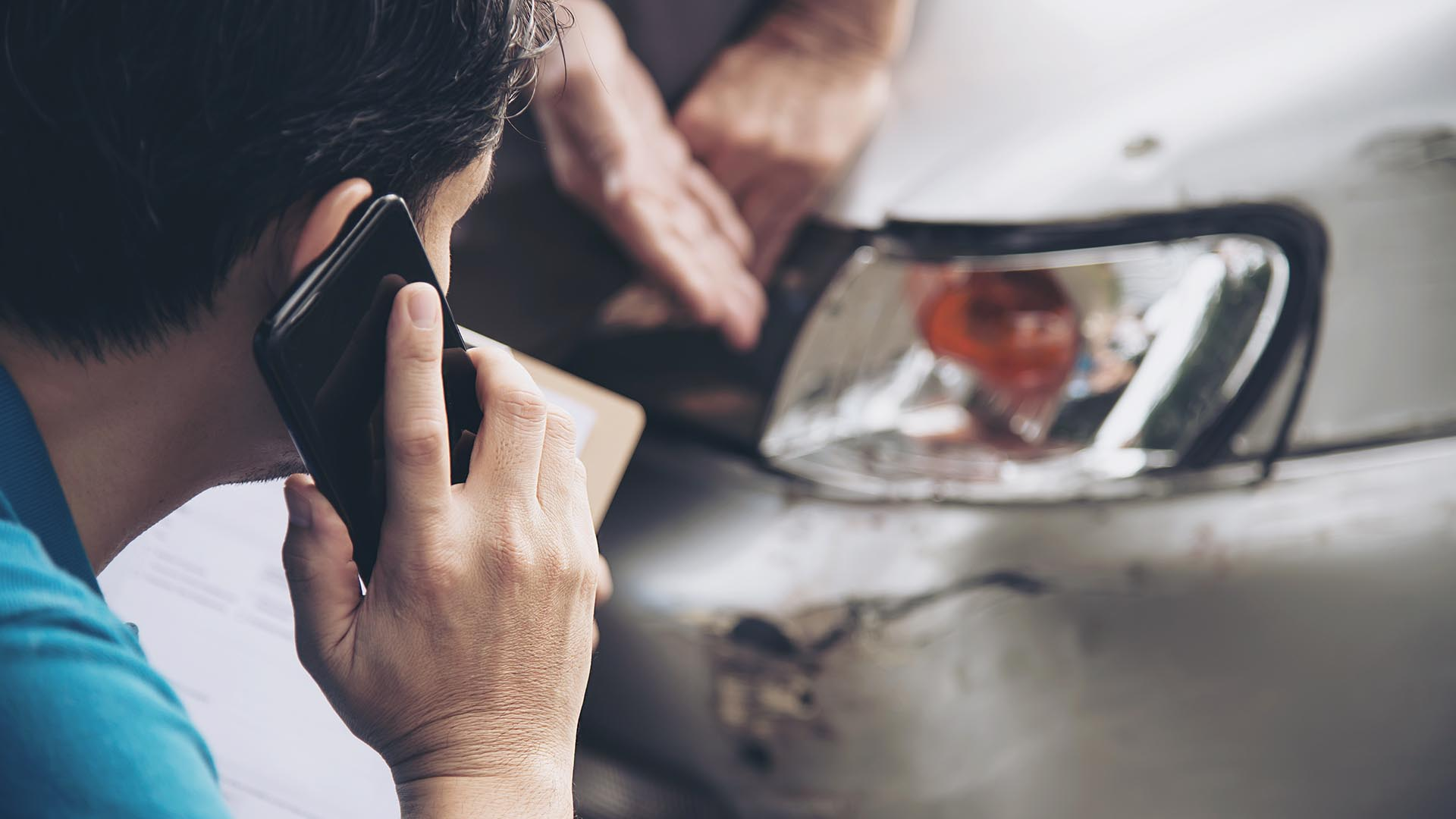 person talking on a cell phone while looking at a damaged vehicle headlight