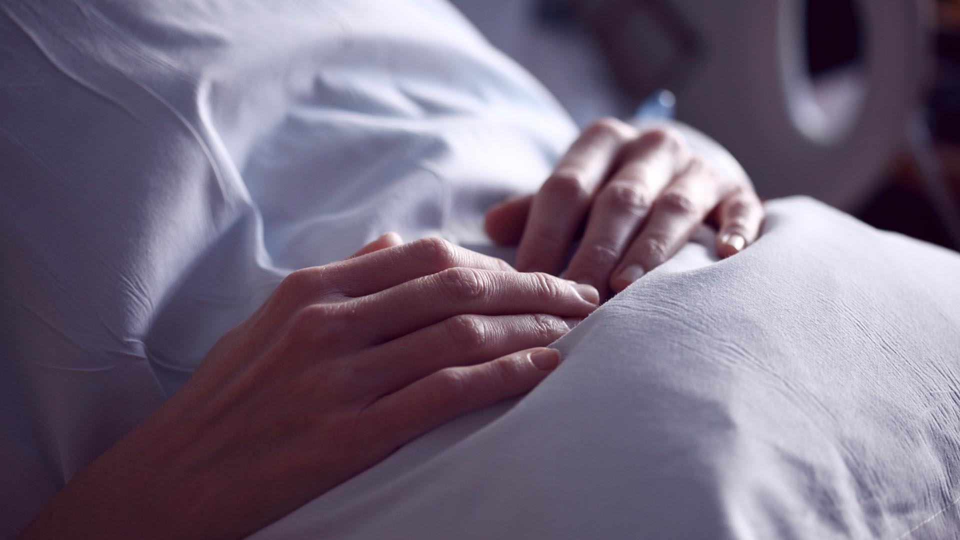 patient's hands clutching a pill in a hospital bed